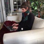 Frau mit Laptop auf Sofa