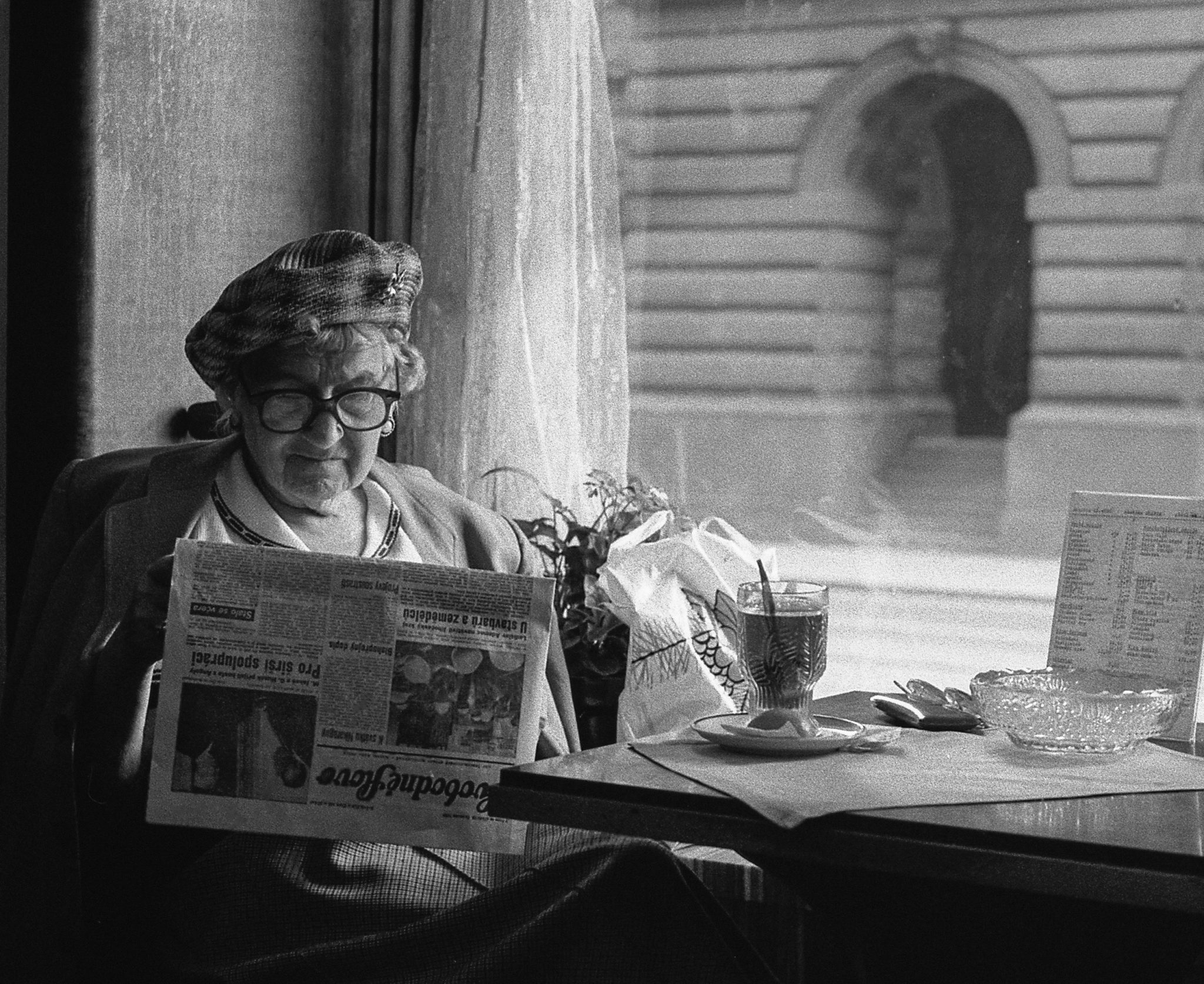 Oma liest Zeitung im Café