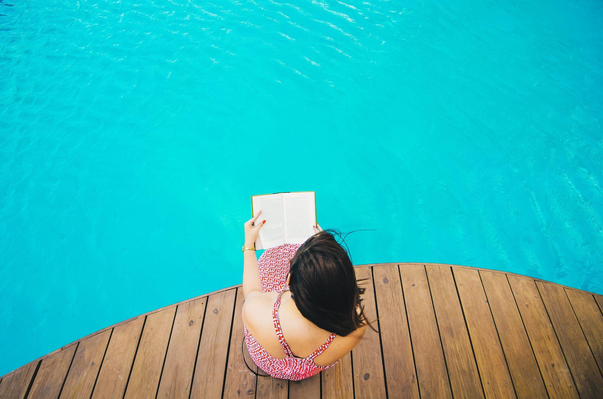 Frau liest Buch am Pool